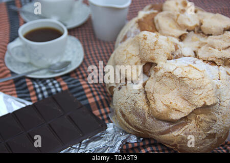 Table with a full service with a typical Valencian mona de Pascua (Easter), coffee and chocolate for two - Stock Photo