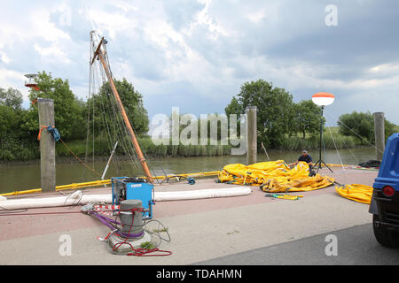 Stadersand, Germany. 14th June, 2019. The mast of the sunken historic sailing ship 'No 5 Elbe' can be seen in the harbour of Stadersand before dark thunderclouds. Salvage preparations are underway. The historic sailing ship, which has only recently been extensively renovated, collided with a container ship on the Elbe and sank. Credit: Bodo Marks/dpa/Alamy Live News - Stock Photo
