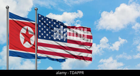 North Korea and United States flag waving in the wind against white cloudy blue sky together. Diplomacy concept, international relations. - Stock Photo