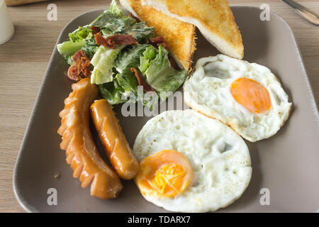 Set of american breakfast with fried eggs and sausage on wood table background. - Stock Photo