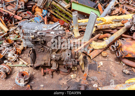 Aged internal combustion engine is placed among rusted parts of obsolete equipment in industrial complex. - Stock Photo