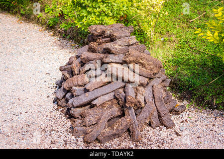 Pile of brown peat bricks drying in sunlight on green grass, fuel to be used in fireplace - Stock Photo