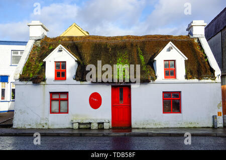 Old ruined and abandoned thatched traditional house with red windows and door in Ireland