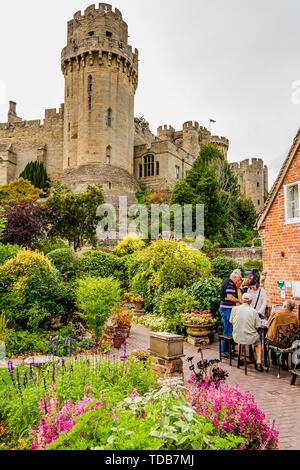 Visitors to The Mill Garden with its view of Caesar's Tower, Warwick Castle. Warwick, UK. Summer 2018. - Stock Photo