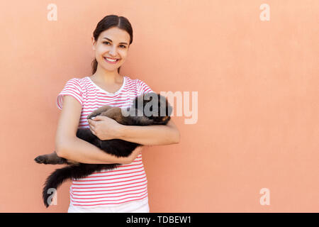 Happy young woman holding her pet puppy on orange background. - Stock Photo