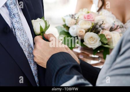 After the wedding ceremony, the groom is hugging a small rose on a jacket. Romantic vacation - Stock Photo