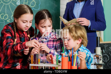 Inspired to work hard. happy children teacher. doing experiments with liquids in chemistry lab. chemistry lab. back to school. kids in lab coat learning chemistry in school laboratory. - Stock Photo
