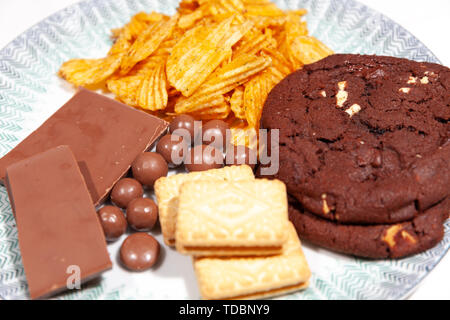 Plate of Triple-Chocolate Cookies,Chocolate covered honeycomb balls, Crinkle cut Crisps, bar of chocolate on a white plate with gre striped edging - Stock Photo