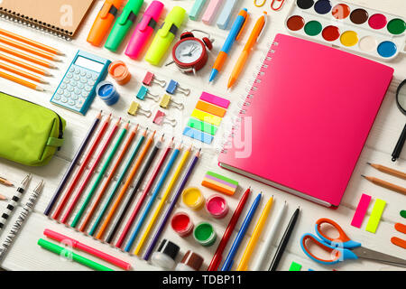 Flat lay composition with school supplies on white wooden background - Stock Photo