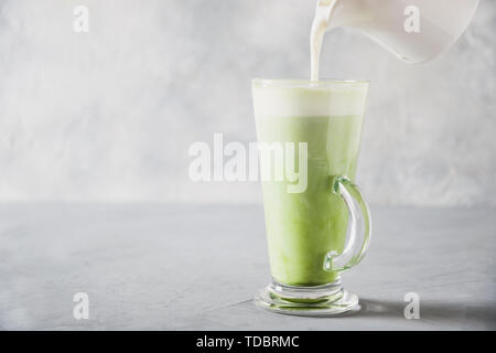 Green matcha tea and pouring milk in latte glass on grey table. Space for text. Close up. Horizontal orientation. - Stock Photo