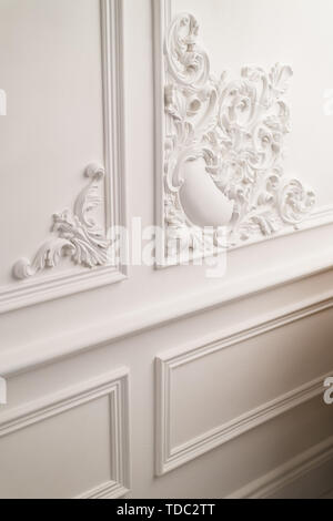 Stucco elements on light luxury wall. White patterned. Roccoco style. Close up. Selective focus. - Stock Photo