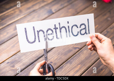 woman cuts white paper with word unethical on table - Stock Photo