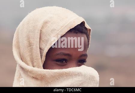 AMHARA REGION, ETHIOPIA, APRIL 22.2019, Beautiful Ethiopian Amhara girl hides her face behind a scarf. Amhara Region, Ethiopia, April 22. 2019 - Stock Photo