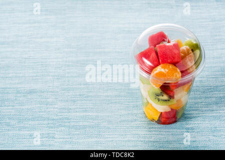 Fresh cut fruit in a plastic cup on blue background - Stock Photo