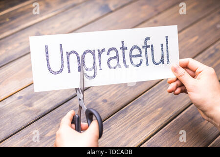 woman cuts white paper with word ungrateful on table - Stock Photo