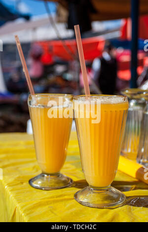 Two glasses of delicious, refreshing freshly made by local people in the street stand, orange juice. Tasty beverage. - Stock Photo