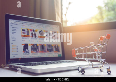 Shopping online concept - Empty shopping cart or trolley and laptop on white table. Shopping service on The online web. with copy space - Stock Photo