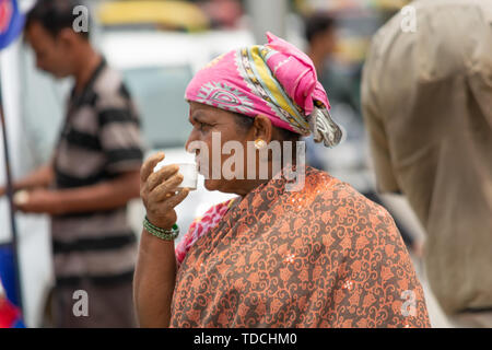 Bangalore, Karnataka India-June 04 2019 : Indian Woman drinking Tea on street after completing the work - Stock Photo