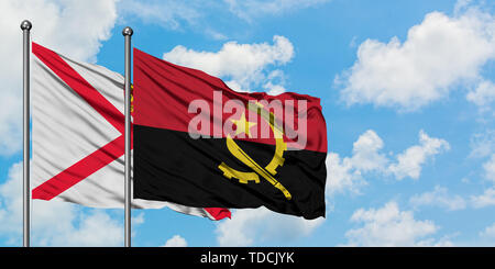 Jersey and Angola flag waving in the wind against white cloudy blue sky together. Diplomacy concept, international relations. - Stock Photo