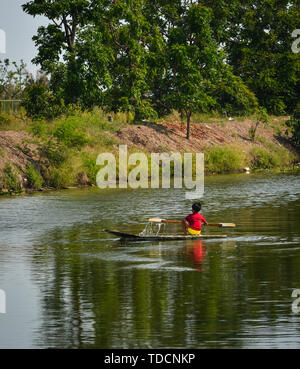 A little boy rowing wooden boat on canal in Bangkok, Thailand. - Stock Photo