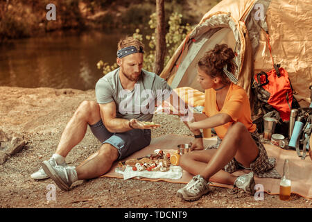 Pleasant hungry young people holding tasty sandwiches - Stock Photo
