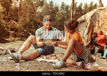 Nice young woman doing a sandwich for her boyfriend - Stock Photo