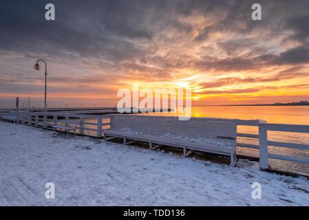 Bench on frozen pier in Sopot, winter seascape. Baltic Sea. Poland. - Stock Photo