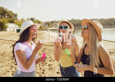 Girlfriends  blowing soap bubbles on the beach. - Stock Photo
