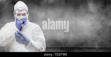 Man Wearing Hazmat Suit and Goggles Holding Test Tube of Blood In Smokey Room Banner with Copy Space. - Stock Photo