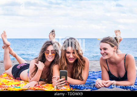 Summer concept with group of three beautiful girls in friendship stay lay down relaxed at the beach speaking and using a smartphone to share her summe - Stock Photo