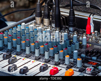 Sound mixer for rock band preparing a concert in the field - Stock Photo