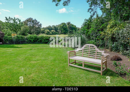 Tranquil english country garden with rural view and wooden bench.  Taken on a sunny morning in Sussex. - Stock Photo