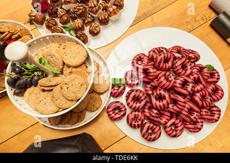 Colorful donuts and variety of sweets laid on a wooden table along with two paper tubes and a black leather bag