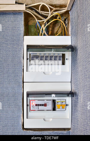 Electrical safety in houses, modern electrical switchboard, fusebox, new electronic electricity meter and old burned problem wiring. Burned out wires  - Stock Photo