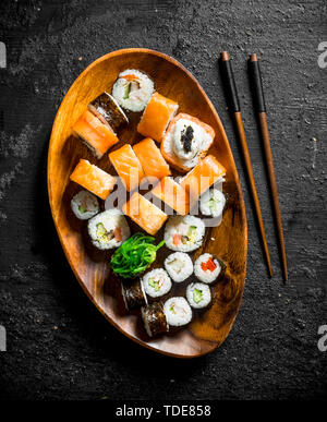 Various sushi rolls with salmon and vegetables on a wooden plate with chopsticks. On black rustic background