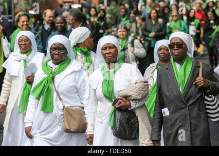 London, UK. 14th June, 2019. Nuns wearing symbolic green scarf take part in a silent marching from St Helen's Church to Grenfell Tower during the commemoration. The Grenfell Tower second anniversary commemoration of the tower block fire. On 14 June 2017, just before 1:00am a fire broke out in the kitchen of the fourth floor flat at the 24-storey residential tower block in North Kensington, West London, which took the lives of 72 people. More than 70 others were injured and 223 people escaped. Credit: SOPA Images Limited/Alamy Live News - Stock Photo