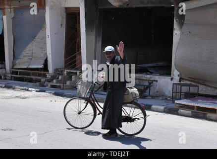 Palmyra, Syria. 14th June, 2019.  A man is seen returning to the city of Palmyra in central Syria on June 14, 2019. The ancient city of Palmyra has seen the vicious attacks and occupation of the Islamic State (IS) two times throughout the Syrian crisis and the people of that ancient oasis city went displaced more than once. After the second liberation of Palmyra in early 2017, the residential part of Palmyra, which has ancient ruins and residential area, were largely damaged. Credit: Xinhua/Alamy Live News - Stock Photo