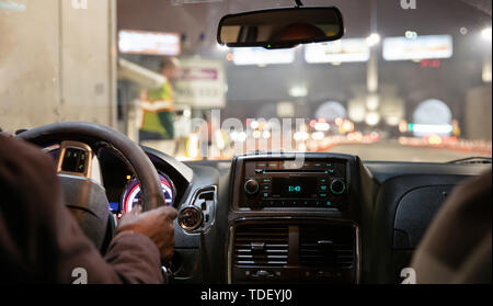 Driving in New York at night. Interior view of taxi cab. Close up view on the dashboard and drivers hand. - Stock Photo