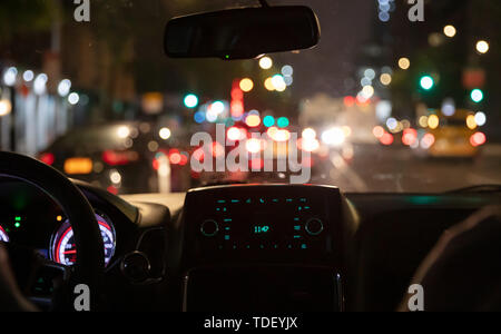 Driving in New York at night. Interior view of taxi cab in traffic. Close up view on the dashboard. Colorful bokeh lights out of the window - Stock Photo