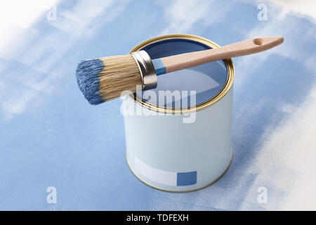 Brush and can of blue paint on painted surface with strokes - Stock Photo