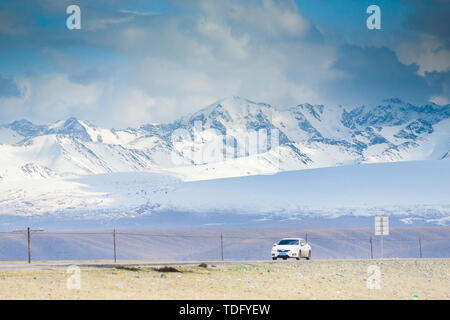 In early spring, a white car moves on the Bayinburu Prairie section of the Doku road, behind a tall, snowy mountain - Stock Photo