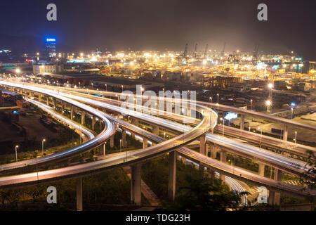 Illuminated and elevated expressway and cityscape at night - Stock Photo