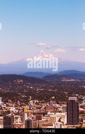 A beautiful aerial shot of an urban city with an amazing snowy mountain in the background - Stock Photo
