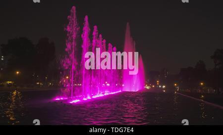 night shot of a purple lit  fountain on the magic water circuit in lima, peru - Stock Photo