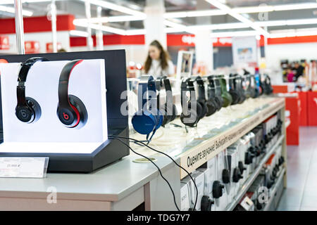 Chelyabinsk Region, Russia - June 2019. Household electrical appliances store M Video. Shelving with goods. Stereo headphones - Stock Photo