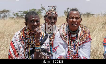 MASAI MARA, KENYA- 26, AUGUST, 2016: close up of three maasai women in traditional dress at koiyaki guiding school graduation day in kenya - Stock Photo
