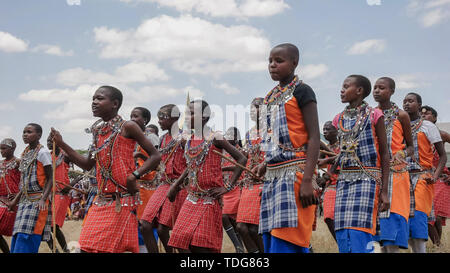 MASAI MARA, KENYA- 26, AUGUST, 2016: low angle view of a group of maasai boys dancing at koiyaki guiding school graduation ceremony in kenya - Stock Photo