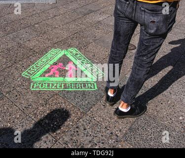 Stencil on pavement and man with wallet on a chain in pocket. Police warning about pickpockets & thieves on sidewalk in Kreuzberg-Berlin - Stock Photo