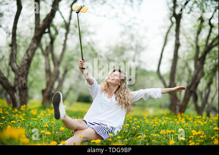 beautiful blonde girl with beautiful hair sits in a field of dandelions and makes selfie - Stock Photo