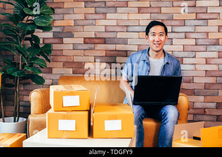 Young Asian male business entrepreneur using computer laptop while packing products into boxes to deliver - Online small business and ecommerce - Stock Photo